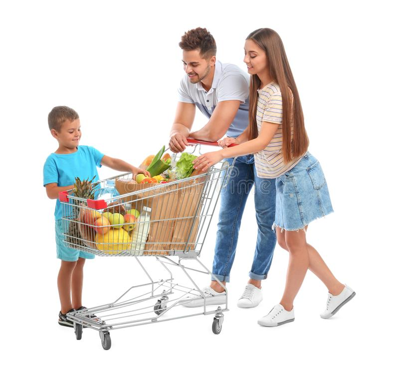 Happy family with full shopping cart on background. Happy family with full shopping cart on white background stock photo