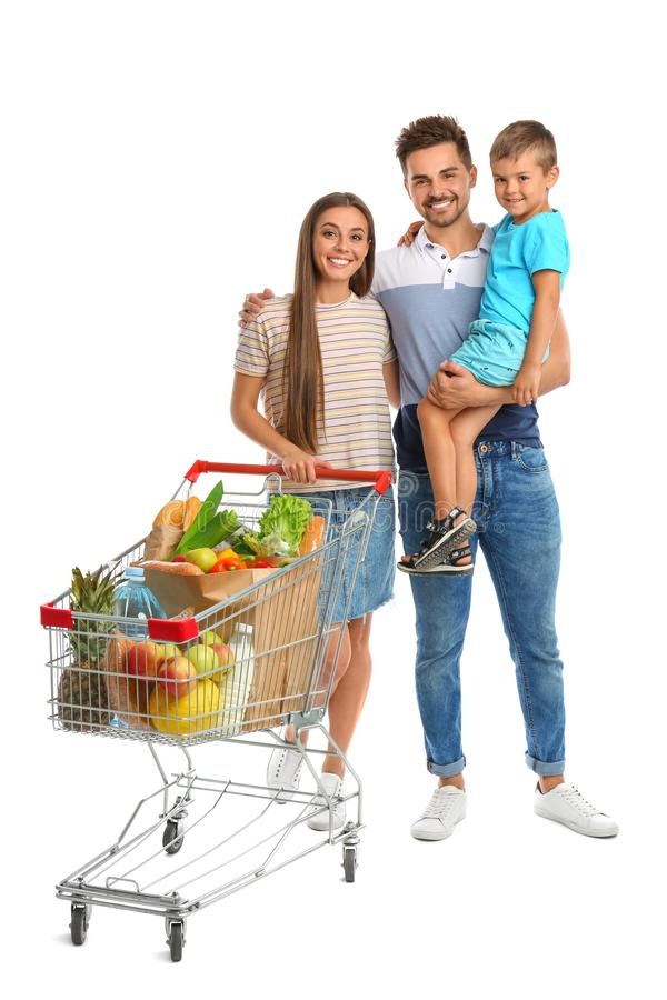 Happy family with full shopping cart on background. Happy family with full shopping cart on white background stock photography