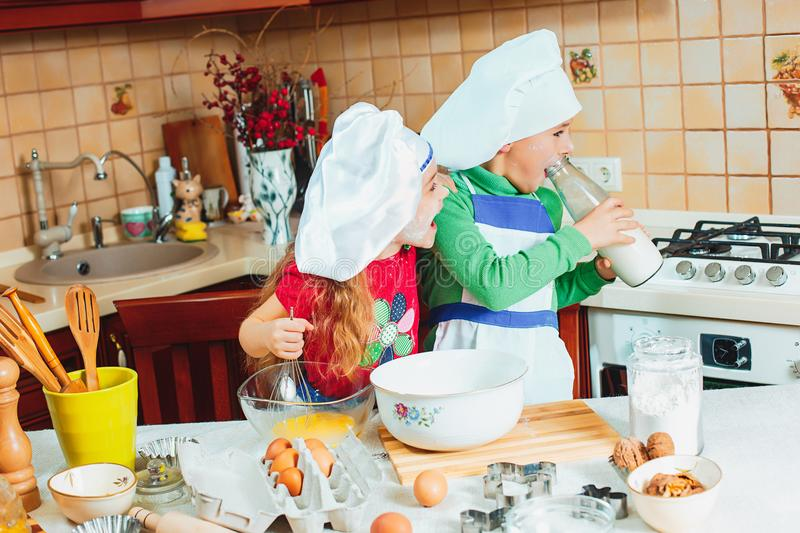 Happy family funny kids are preparing the dough, bake cookies in the kitchen. The happy two funny kids are preparing the dough, bake cookies in the kitchen stock photos