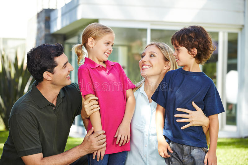 Happy family in garden of a house. Happy family laughing with two children in garden of a house stock photo
