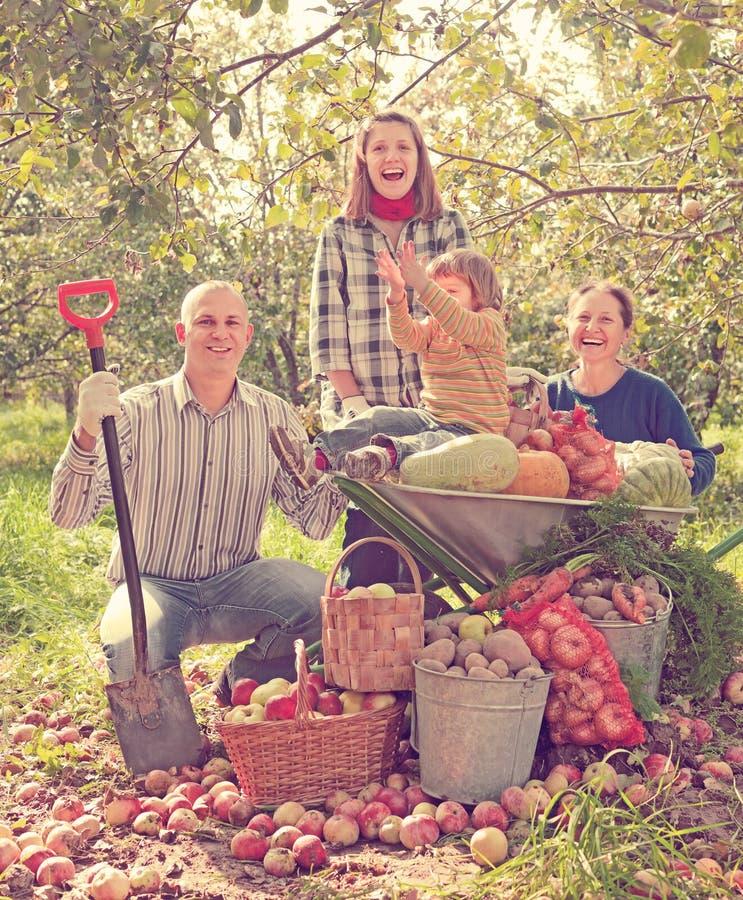 Happy family in garden. Happy family with vegetables harvest in garden stock image