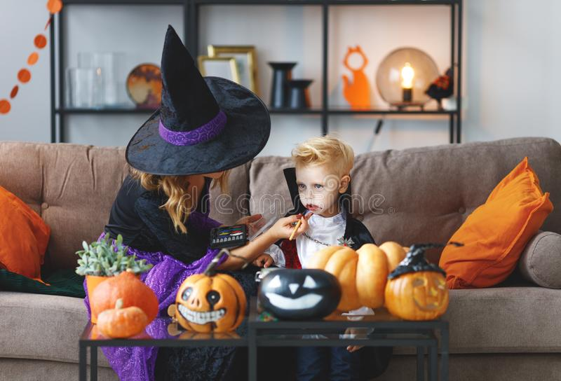 Happy family getting ready for halloween make make-up. Happy family mother and son getting ready for halloween make make-up royalty free stock photography