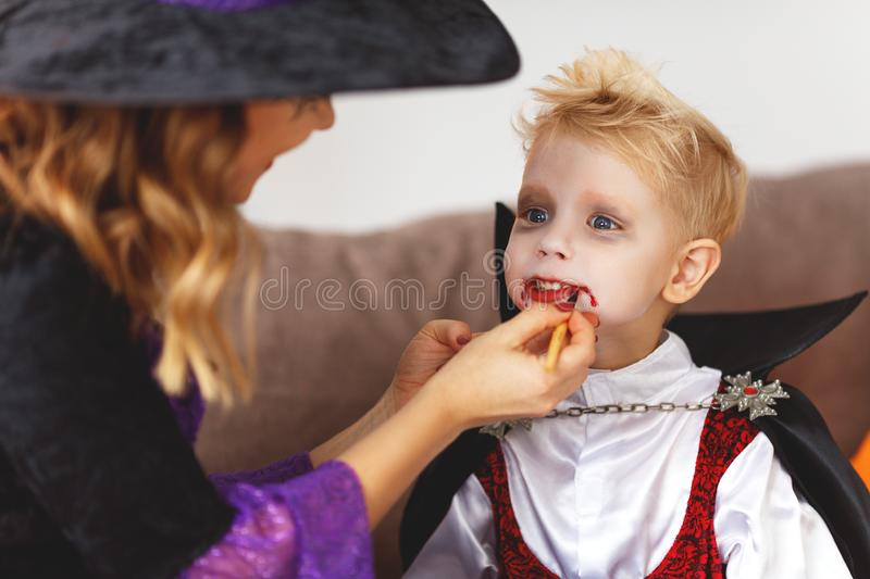 Happy family getting ready for halloween make make-up. Happy family mother and son getting ready for halloween make make-up stock photography