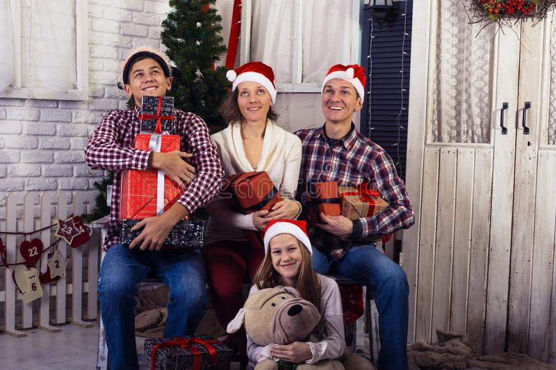 Happy family, with gifts in hands. Sitting in front of a Christmas tree together, in anticipation of the merry Christmas stock images