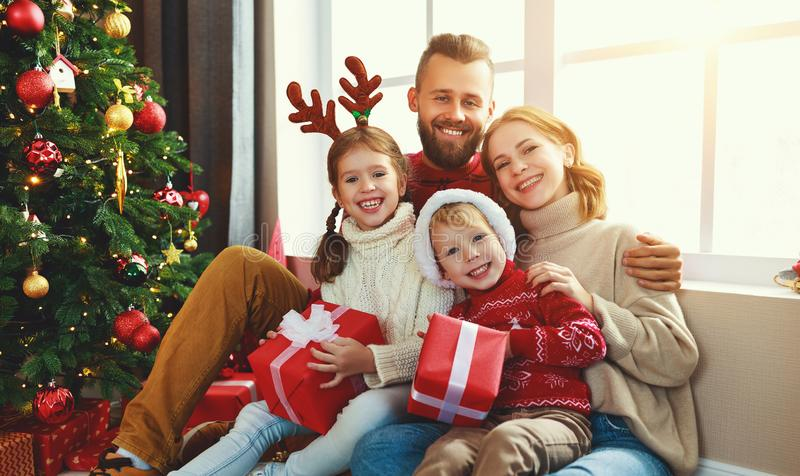 Happy family with gifts near   Christmas tree at home. Happy family with gifts near festive Christmas tree at home royalty free stock photography