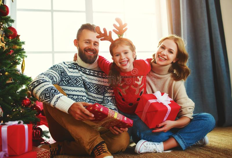 Happy family with gifts near   Christmas tree at home stock image
