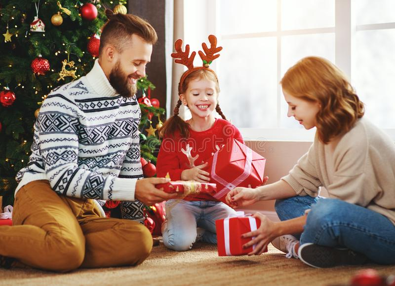 . happy family with gifts near   Christmas tree at home stock images