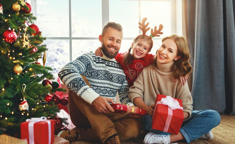 Happy family with gifts near   Christmas tree at home. Happy family with gifts near festive Christmas tree at home royalty free stock image