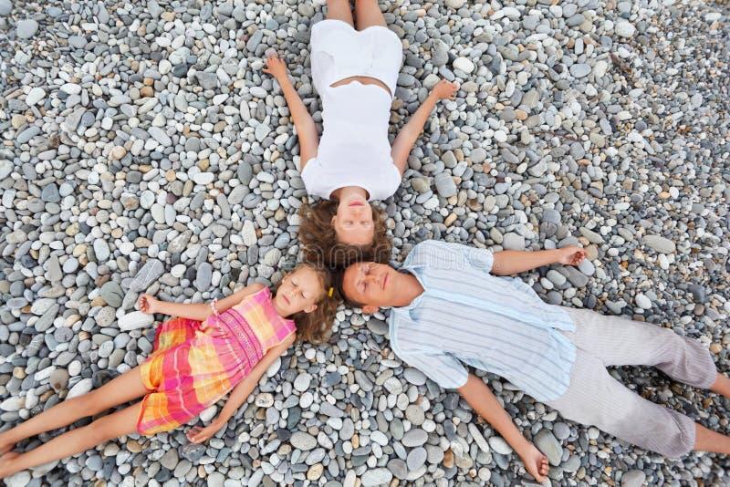 Happy family with girl lying on beach, closed eyes stock photos