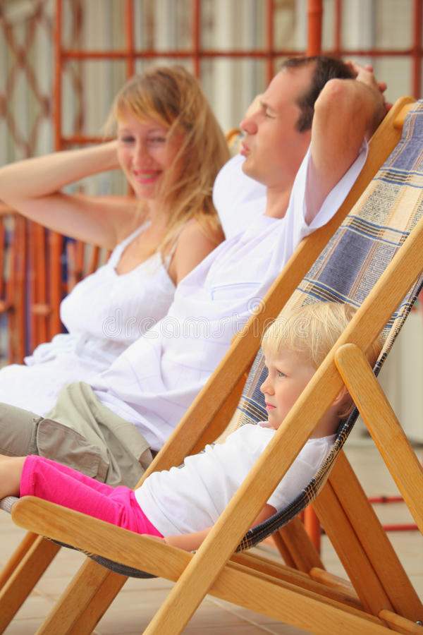 Happy family with girl reclining on chaise lounges