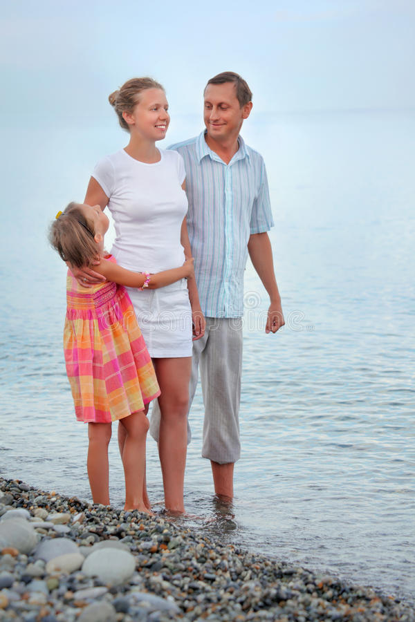 Happy family with girl standing on beach, evening