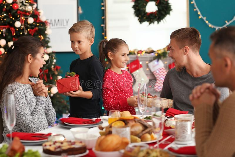 Happy family giving each other presents during Christmas dinner at home stock images