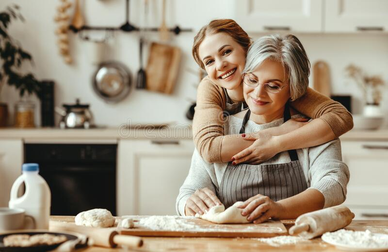 Happy family grandmother  old mother mother-in-law and daughter-in-law daughter cook in kitchen, knead dough, bake cookies stock image
