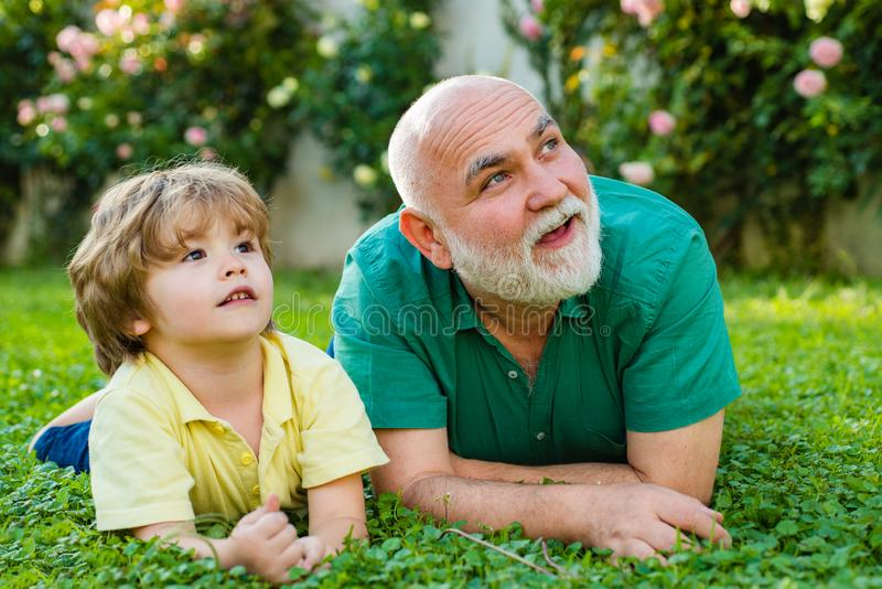 Happy family Grandson hugs his grandpa on holiday. Two generation - weekend together. Grandson embrace his grandfather royalty free stock images