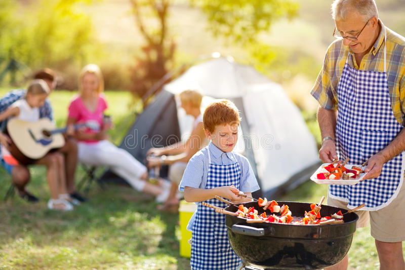 Happy family grilling meat on a barbecue. Autdoor stock photos