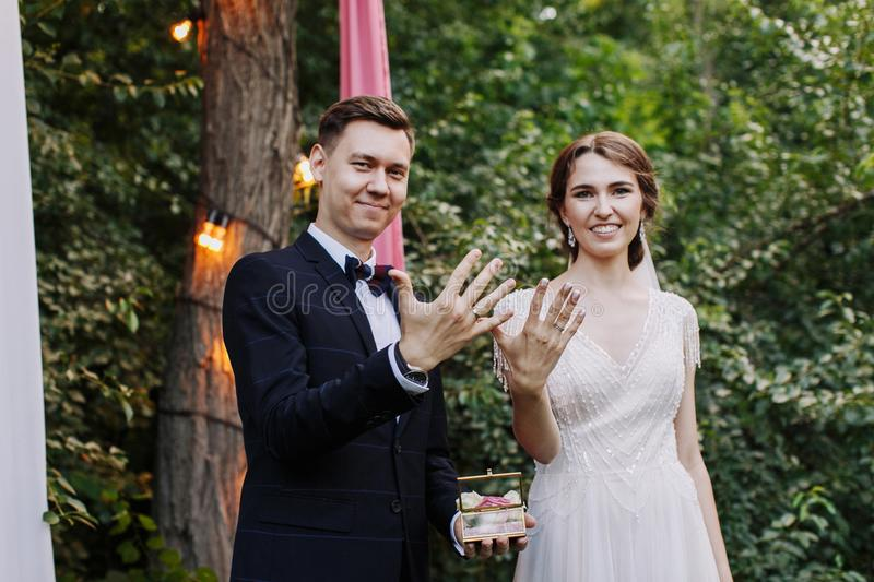 Happy family of groom and bride at wedding day ceremory with arch and retro lightbulb on background shows their hands. With rings. Smiling newlyweds. Concept of stock photography