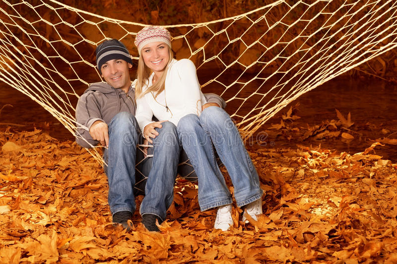Happy family in hammock. Photo of young happy family lying down in hammock on backyard, wife with husband spending leisure time in autumn park, cute teenagers royalty free stock photos