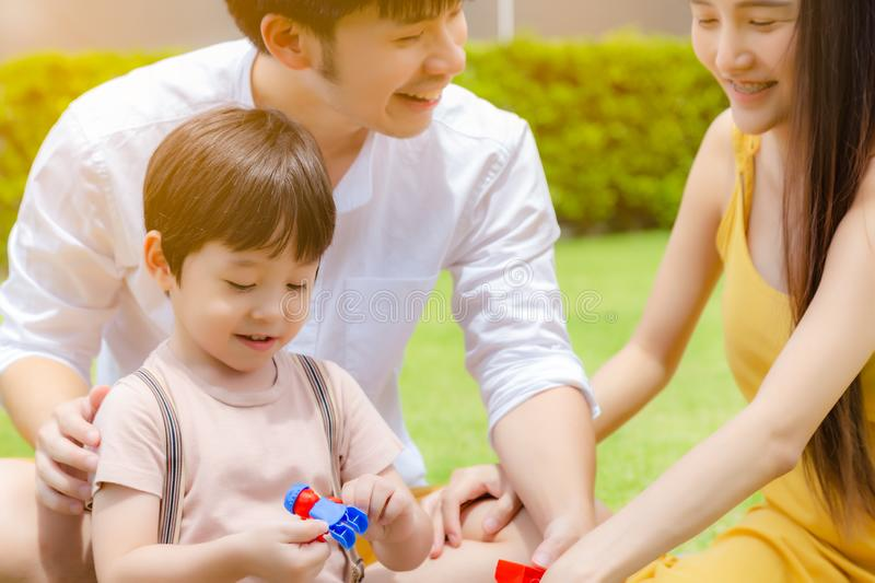 Happy family. Handsome little boy or son playing toy with dad, mother at beautiful park. Cute child get happiness and enjoy life. royalty free stock images
