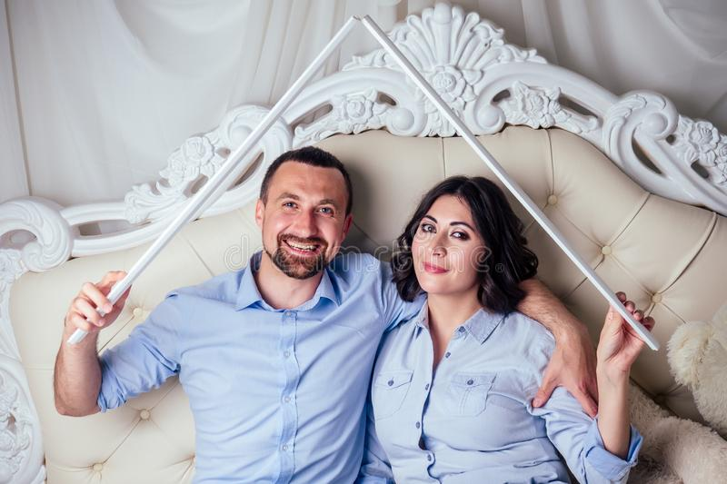 Happy family handsome man and charming woman together make the roof on bed in bedroom . concept of buying a house by stock images