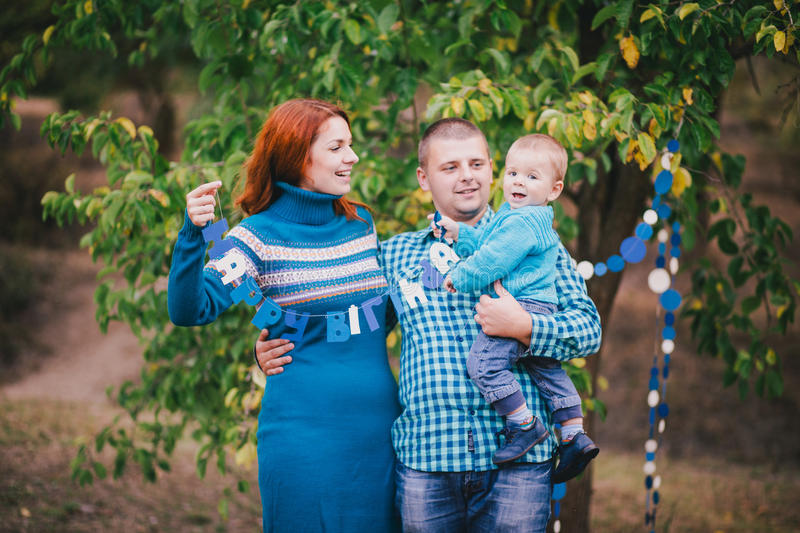 Happy family have birthday party with blue decorations in forest. Happy family having birthday party with blue decorations in an autumn forest stock image