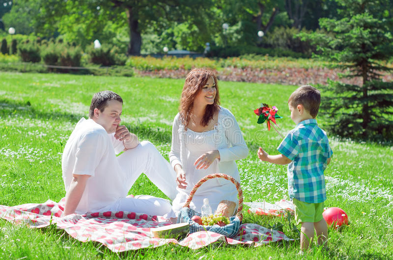 Happy family have picnic. In the park stock image