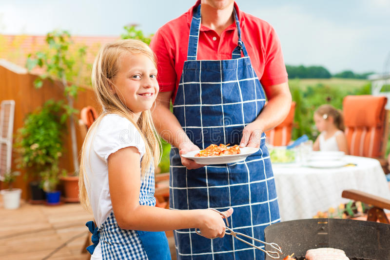 Happy family having a barbecue. In summer; the father and a child standing at the grill stock photography