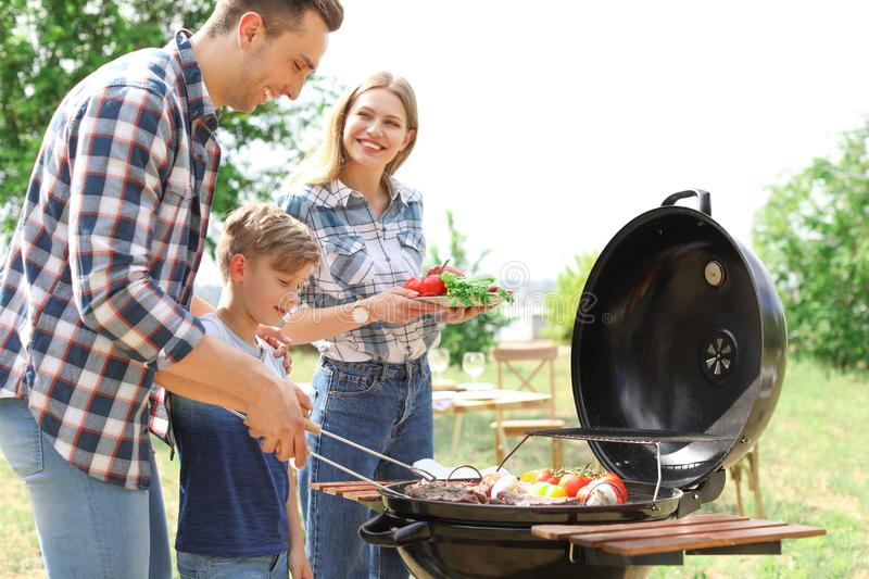 Happy family having barbecue with grill outdoors. Happy family having barbecue with modern grill outdoors stock photos