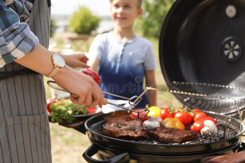 Happy family having barbecue with modern grill. Outdoors royalty free stock photography