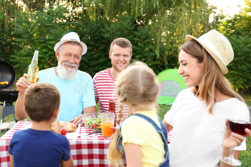 Happy family having barbecue in park. On sunny day stock image