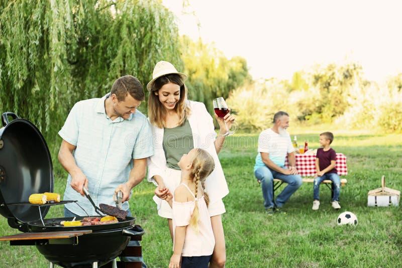 Happy family having barbecue on sunny day royalty free stock photography