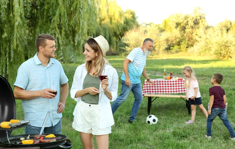 Happy family having barbecue on sunny day royalty free stock photo