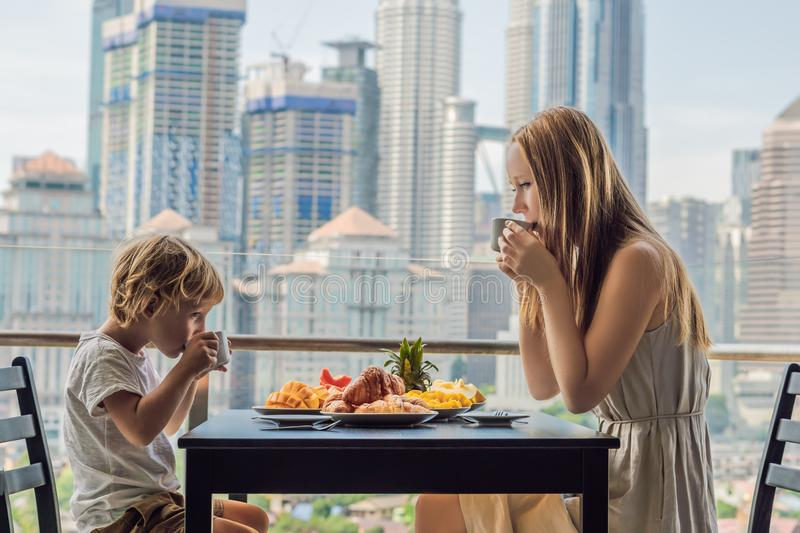 Happy family having breakfast on the balcony. Breakfast table with coffee fruit and bread croisant on a balcony against. The backdrop of the big city royalty free stock image