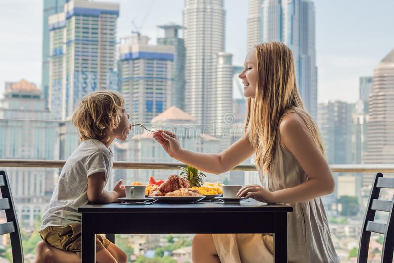 Happy family having breakfast on the balcony. Breakfast table with coffee fruit and bread croisant on a balcony against. The backdrop of the big city royalty free stock photo