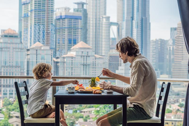 Happy family having breakfast on the balcony. Breakfast table with coffee fruit and bread croisant on a balcony against. The backdrop of the big city stock photography