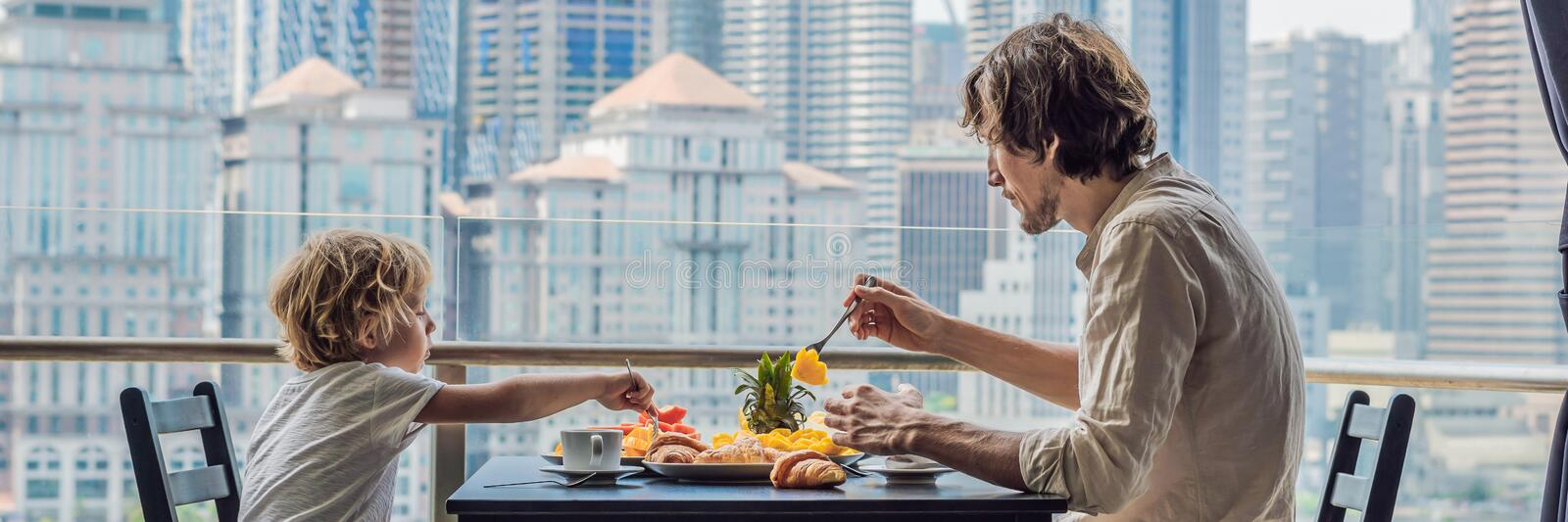 Happy family having breakfast on the balcony. Breakfast table with coffee fruit and bread croisant on a balcony against. The backdrop of the big city. BANNER stock images