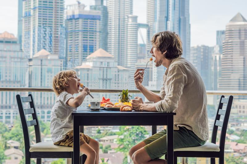 Happy family having breakfast on the balcony. Breakfast table wi. Th coffee fruit and bread croisant on a balcony against the backdrop of the big city stock photos