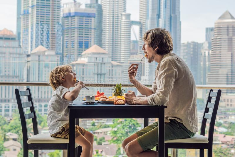 Happy family having breakfast on the balcony. Breakfast table with coffee fruit and bread croisant on a balcony against the backdr. Op of the big city stock image