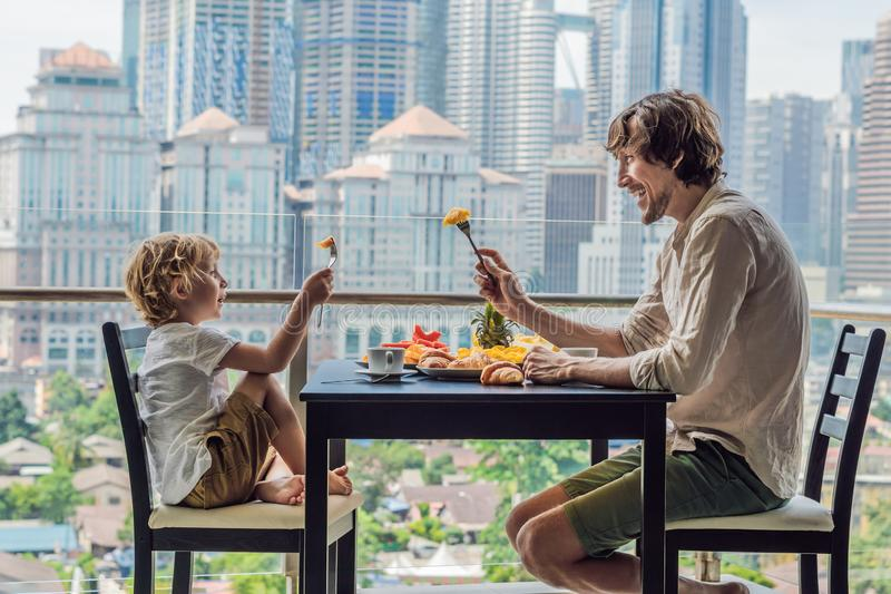 Happy family having breakfast on the balcony. Breakfast table with coffee fruit and bread croisant on a balcony against. The backdrop of the big city royalty free stock images