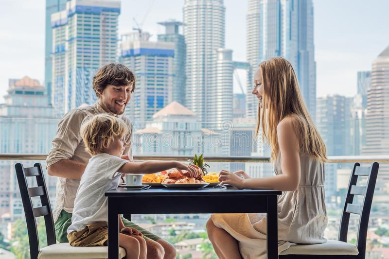 Happy family having breakfast on the balcony. Breakfast table with coffee fruit and bread croisant on a balcony against. The backdrop of the big city stock photo