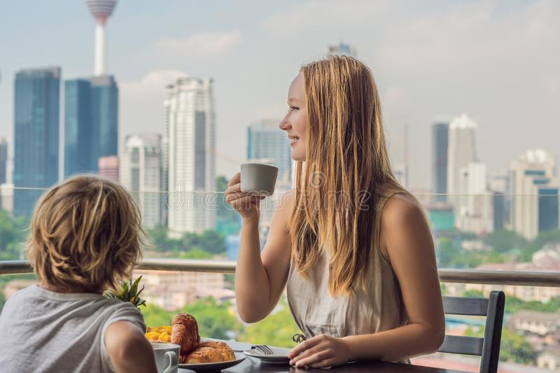 Happy family having breakfast on the balcony. Breakfast table with coffee fruit and bread croisant on a balcony against. The backdrop of the big city royalty free stock photos