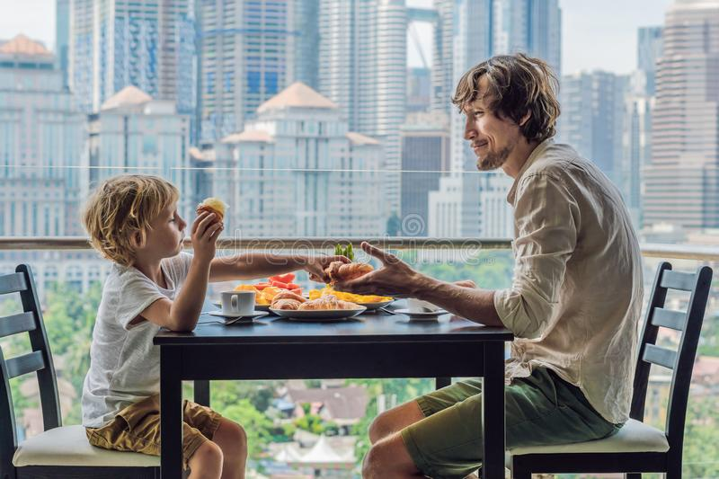 Happy family having breakfast on the balcony. Breakfast table with coffee fruit and bread croisant on a balcony against. The backdrop of the big city royalty free stock photography