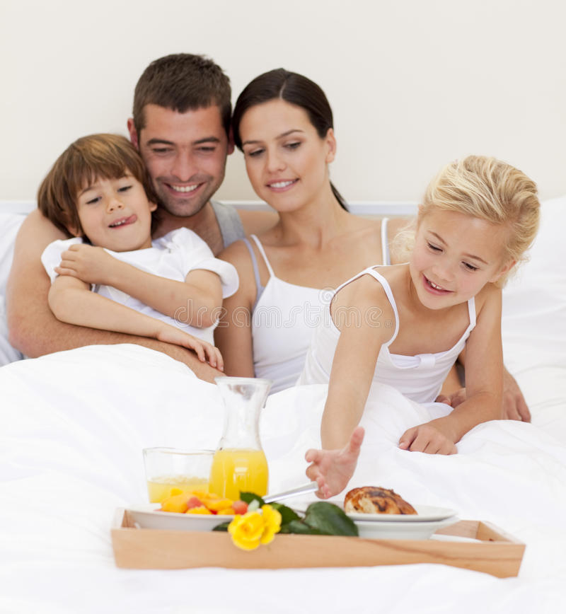 Happy family having breakfast in bedroom. Happy family having nutritive breakfast in bedroom royalty free stock photo