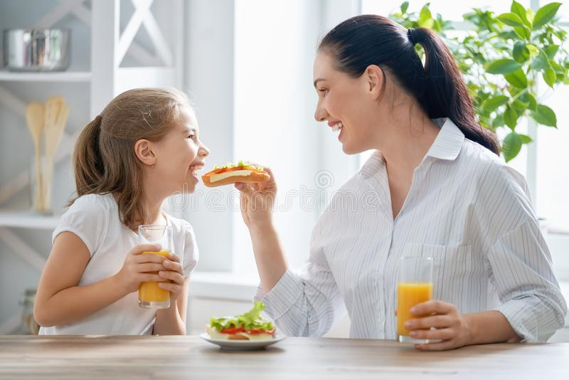 Happy family having breakfast. Healthy food at home. Happy family in the kitchen. Mother and child daughter are having breakfast stock image