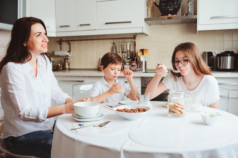 Happy family having breakfast at home. Mother with two kids eating in the morning in modern white kitchen. Happy family having breakfast at home. Mother with two stock photos