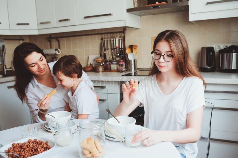 Happy family having breakfast at home. Mother with two kids eating in the morning in modern white kitchen. Happy family having breakfast at home. Mother with two royalty free stock photography