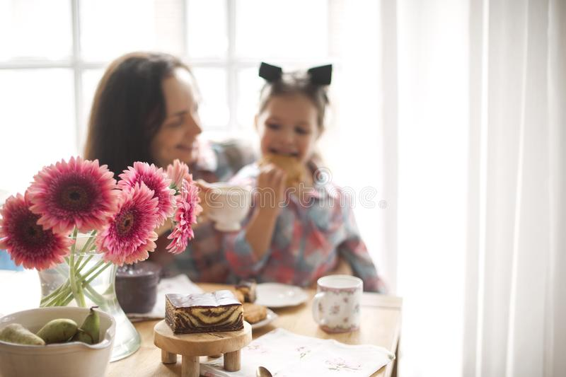 A happy family is having breakfast at home by the window at the table. Flowers and coffee. Mom and daughter. copy space stock photo