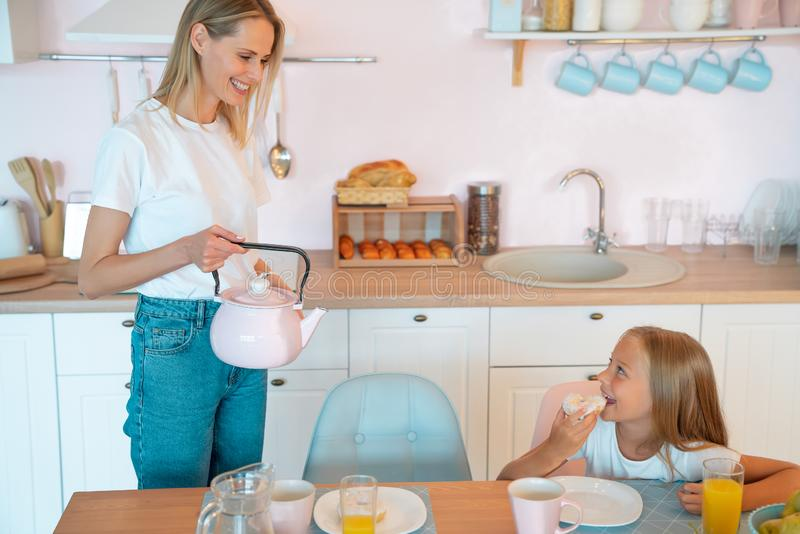 Happy family having breakfast in the kitchen. Young mom and her cute little daughter are smiling and preparing breakfast at home royalty free stock photos
