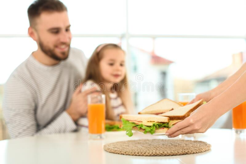 Happy family having breakfast with sandwiches in kitchen royalty free stock photo