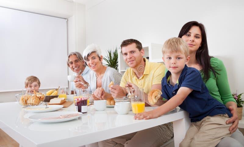Happy family having breakfast together royalty free stock photos