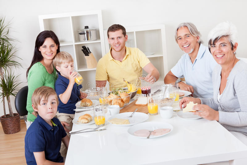 Happy family having breakfast together stock images